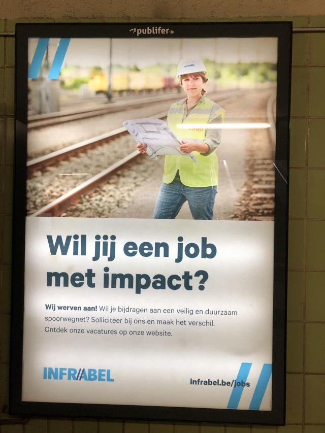 """Une affiche publicitaire pour Infrabel, montrant une jeune femme ingénieur. Le slogan en néerlandais, disant """"Voudriez-vous un travail avec de l'impact?"""""""