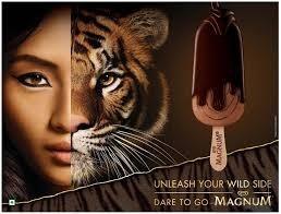 """Cette publicité montre le visage d'une jeune femme d'origine asiatique. La moitié de son visage est remplacée par la moitié d'une tête de tigre. Le slogan qui accompagne l'image est le suivant : """"Unleash your wild side. Dare to go Magnum"""" (""""Libérer votre côté sauvage. Osez Magnum"""")."""