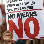 Protestbord met volgende tekst in het Engels: 'Whatever we wear. Wherever we go. Yes means yes. No means NO.