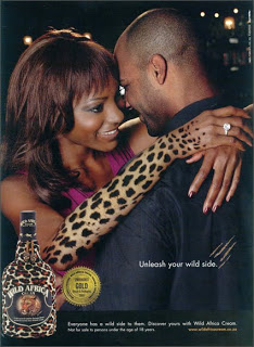 Een jong koppel van Afrikaaanse afkomst omhelst elkaar. Op de arm van de vrouw is een luipaard motief aangebracht, net als op de fles (onderaan in beeld) met alcohol van het merk 'Wild Africa'. De slogan luidt: 'Unleash your wild side'.