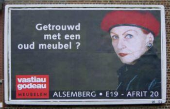 """Reclame voor een meubelzaak. Een oudere streng kijkende vrouw is in beeld, met naast haar de slogan: """"Getrouwd met een oud meubel?"""""""