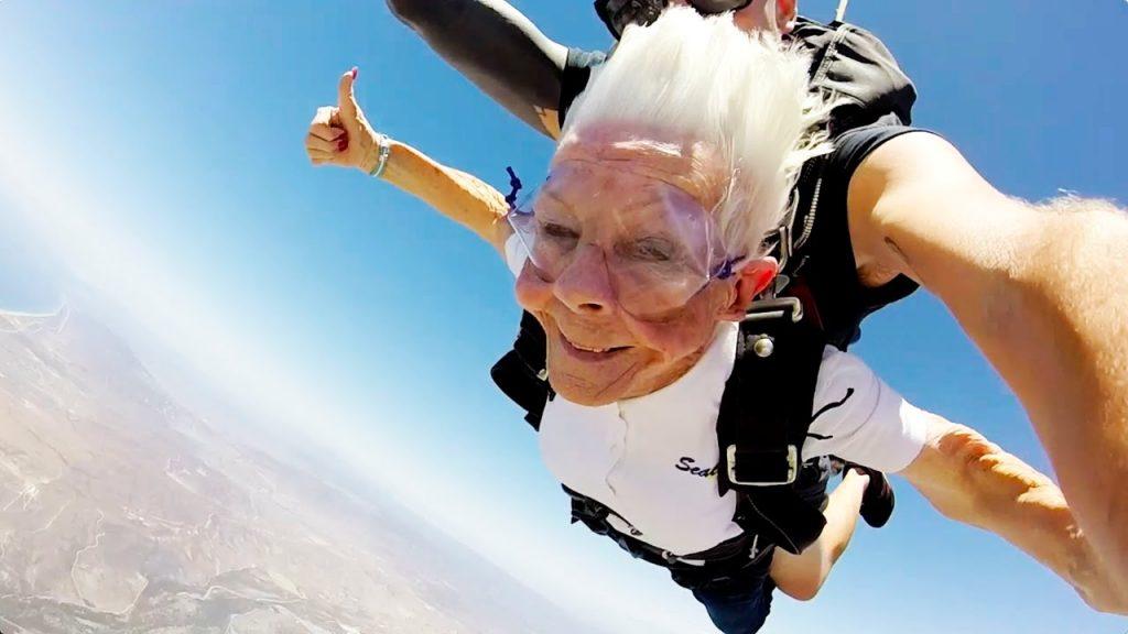 Oudere vrouw springt duo-parachute.