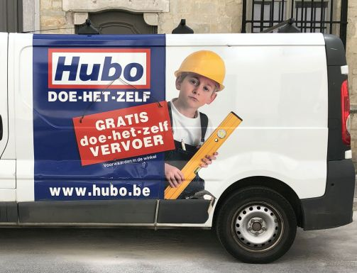 Een advertentie voor een doe-het-zelf zaak is aangebracht op de zijkant van een bestelwagen. De advertentie toont een jongetje van een jaar of 7 in blauwe werkoverall, een veiligheidshelm op en een waterpas in de hand.