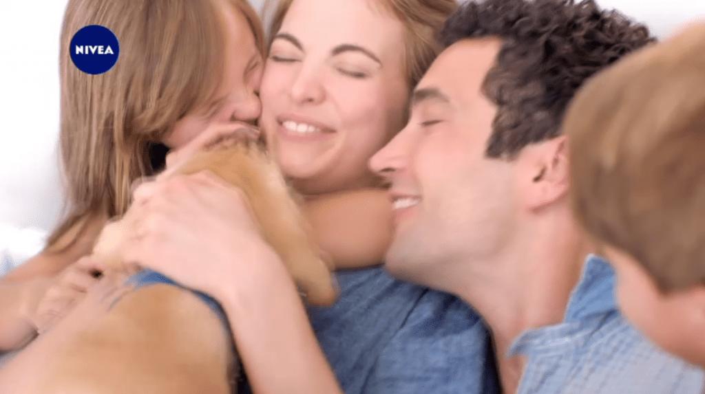 Een screenshot uit een tv-spot voor een huidverzorgingsproduct. In close-up: een jong wit hetero gezin met twee kinderen en een hond in de zetel. Ze knuffelen elkaar.