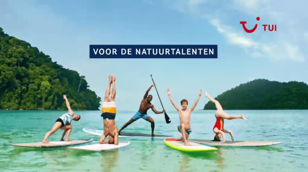Een advertentie voor een zee, strand- en zonvankantie. In beeld drie witte mannen, één witte vrouw en één zwarte man op een surfboard in zee in een exotische baai. De vier witte personen bevinden zich op de voorgrond, de enige zwarte man op de achtergrond.