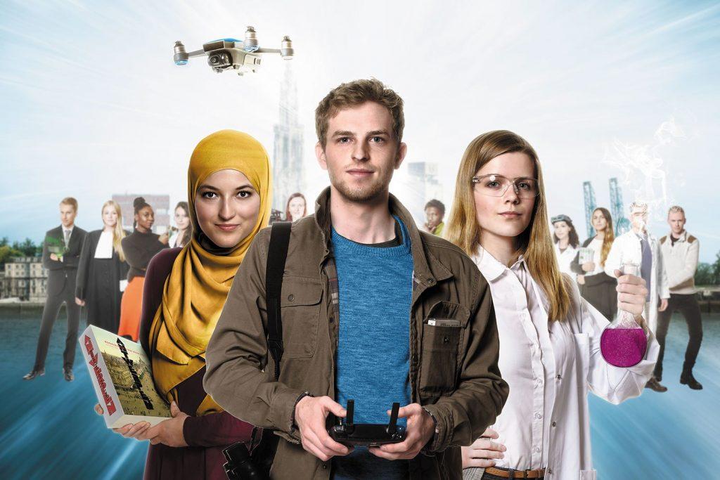 Een advertentie voor een hogeschool. In beeld, op de voorgrond: een witte jonge man. Hij bestuurt een drone. Links achter de jonge man staat een jonge vrouw met een hoofddoek. Ze heeft een cursus in de hand. Rechts achter de man staat een jonge witte vrouw. Ze heeft een proefbuis in de hand.