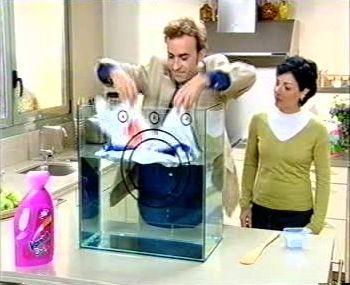 Een man demonstreert aan een vrouw hoe het wasproduct waarvoor reclame wordt gemaakt, beter vlekken verwijdert dan het onbekende product.