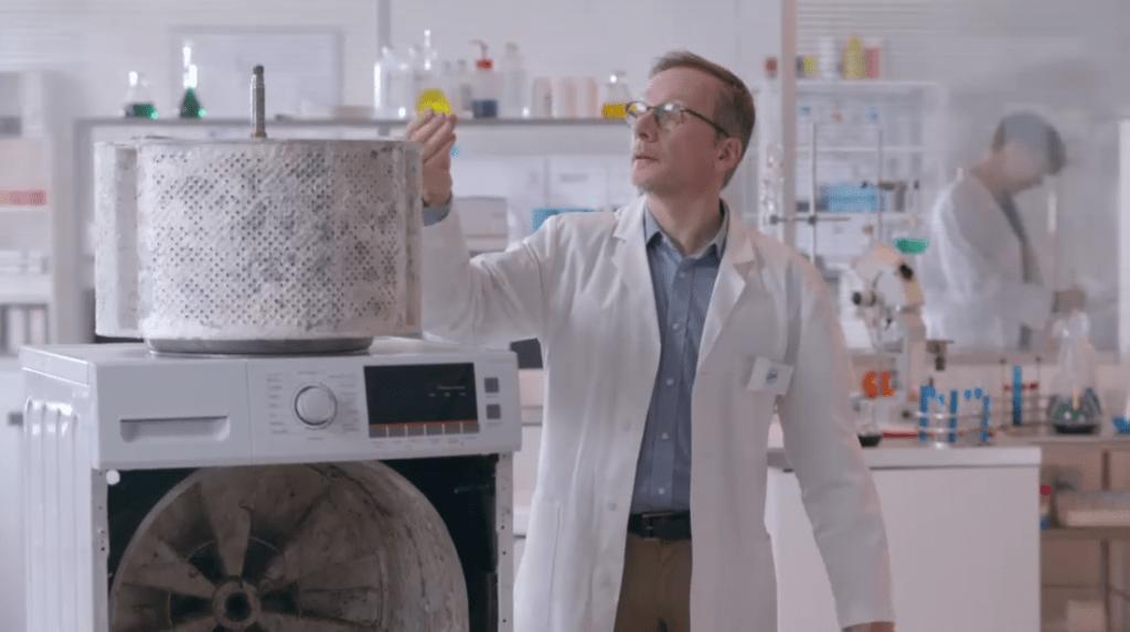 Een man in witte schort staat naast een gedemonteerde wasmachinetrommel. Screenshot uit tv-spot voor Calgon, 2018