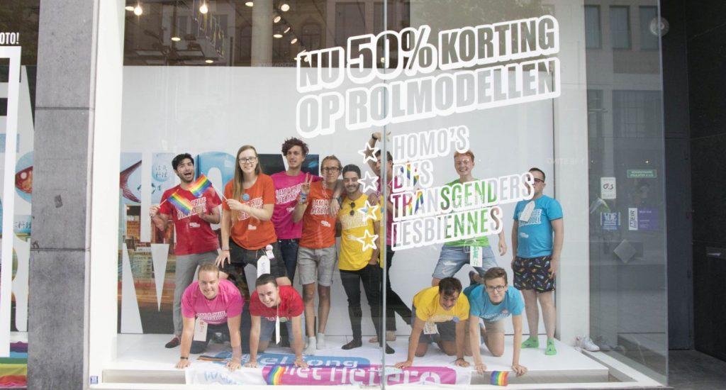 """Jonge holebi's voeren actie in de etalage van een winkelketen. De slogan luidt: """"Nu 50% korting op alle rolmodellen"""""""